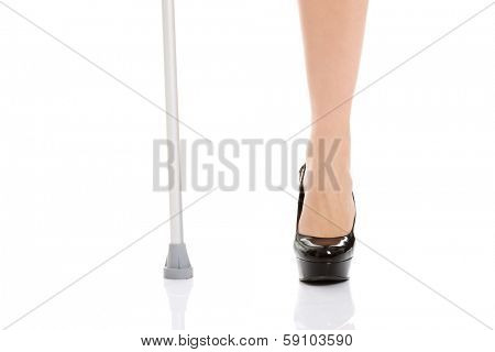 Woman's leg and a crutch. Disabled concept. Isolated on white.