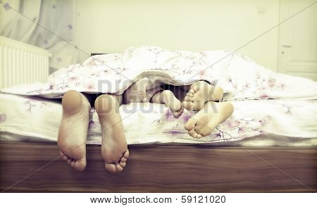 Tree pairs of legs of the happy family in bed - father, mother and baby