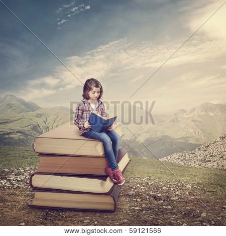 Girl reading a book on a stack of books