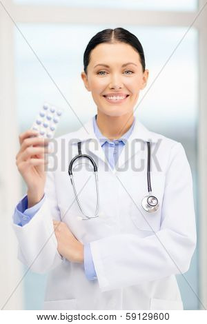 healthcare, pharmacy and medicine concept - smiling young doctor with pills and sthethoscope in cabinet