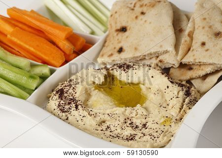 A dip tray with hummus, bread, carrot sticks, celery and cucumber.