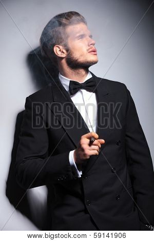young elegant fashion man in tuxedo and bow tie blowing his smoke from his cigar and looking away