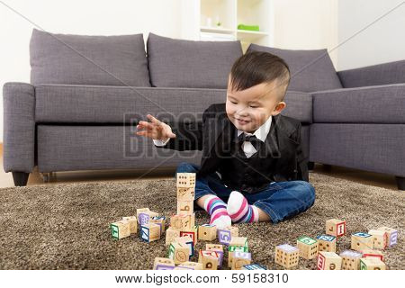 Little boy playing toy block at home