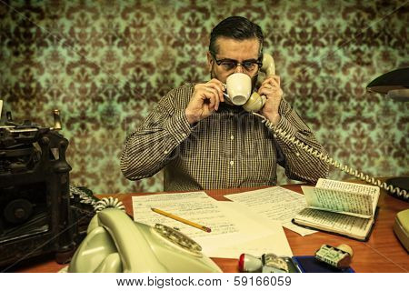 Office Employee With Glasses Sipping Coffee While Talking On The Phone In The 1960S