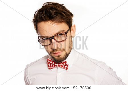 Old-fashioned nerdy businessman wearing a red and white polka dot bow tie looking over the top of his glasses , isolated on white