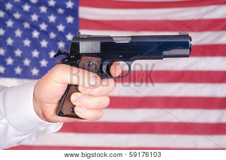 close up of a mans hand holding a 45 ACP 1911 over an American flag