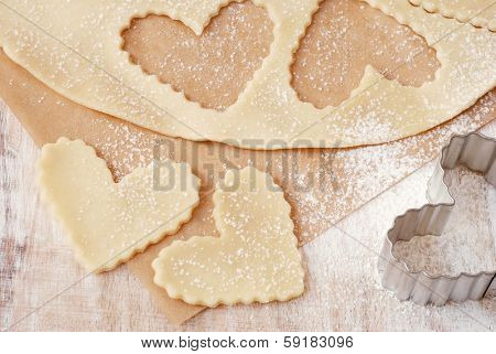 Freshly cut out heart shaped cookies with metal cookie cutter on parchment paper dusted with flour.