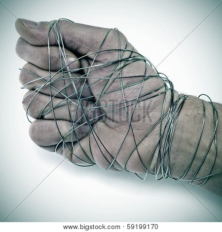 man hand tied with wire, as a symbol of oppression or repression