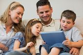 Family of four using digital tablet together on sofa at home poster