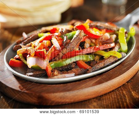 mexican beef fajitas in iron skillet with tortillas in background