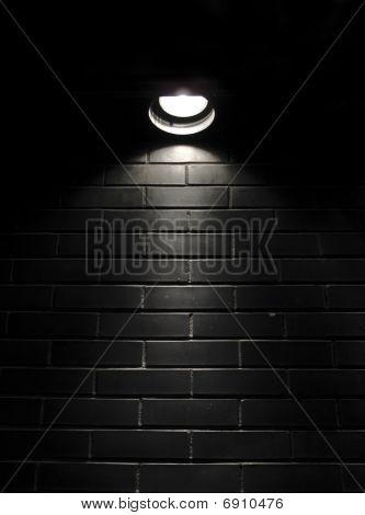Spotlight On A Black Brick Wall
