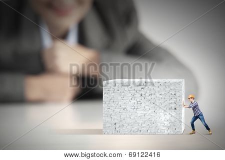 Businesswoman looking at miniature of builder pushing wall poster