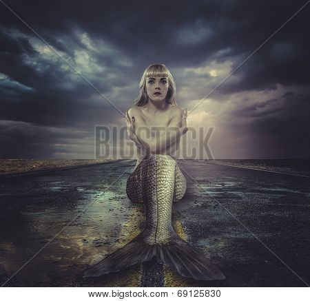 naked mermaid sitting on a deserted road