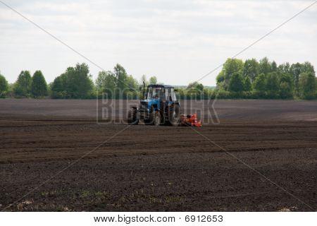 Tractor cultivating potato field (rural scene)