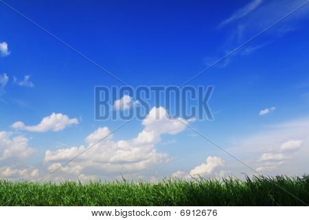 Stripe of rich green grass against blue sky background