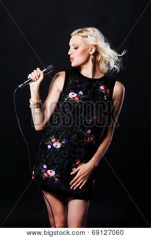 Beautiful blonde singing woman with microphone. Singer. Karaoke song