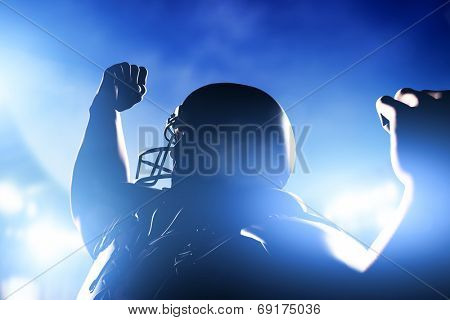 American football player celebrating score and victory. Night stadium lights poster