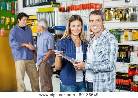 Portrait of happy couple buying tool set in hardware store with people hand shaking in background
