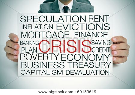 a businessman holding a signboard with different terms related to the economic crisis concept