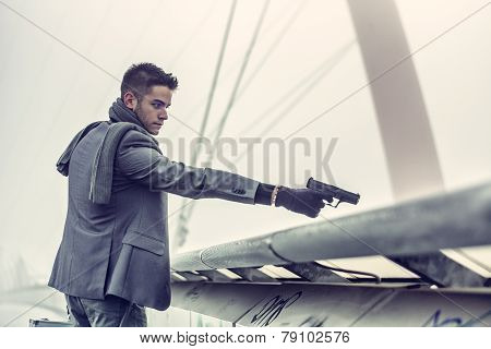 Young detective or policeman or mobster firing a gun