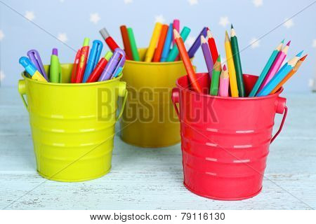 Three plastic cups with different pens, pencils and markers on color wooden table on color wooden table and blue background with printed stars poster