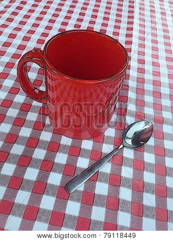 red mug and a spoon on a vichy squared tablecloth