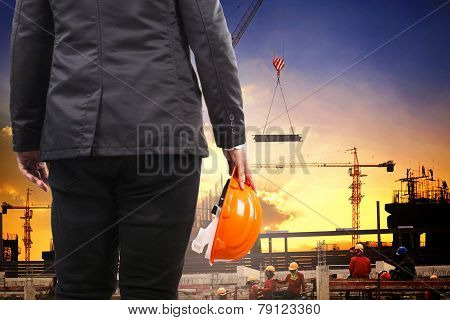 Engineering Man Holding Safety Helmet And Working In Building Construction Site Against Builting Str