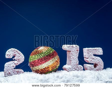 Frosted 2015 New Year digits and glistering ball over dark blue background