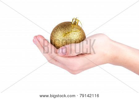 Hand holds a gold Christmas ball