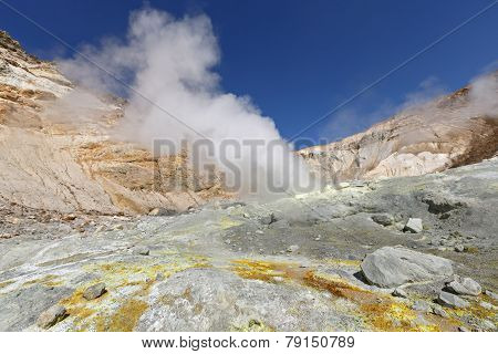 Volcanic landscape of Kamchatka: brimstone and fumarole field in crater of active Mutnovsky Volcano. Russia Far East Kamchatka Peninsula. poster