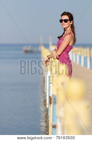 Pretty girl on vacation i standing at a pier enjoying sunshine