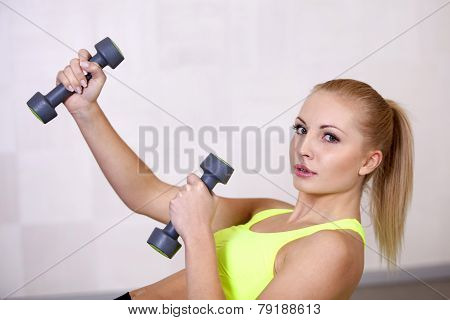 Active beautiful sports girl lifting dumbbells doing workout in a fitness club or gym
