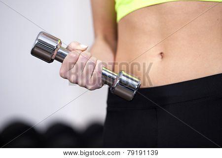 Closeup of woman at the gym lifting free weights