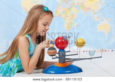 Little girl studies the solar system in geography class - looking at the scale model of planets