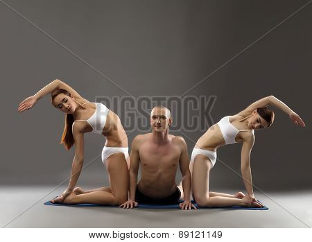 Image of man and girls practicing yoga threesome