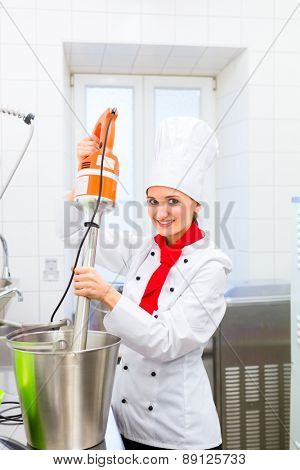 Female Chef preparing ice cream with food processor in gastronomy parlor kitchen