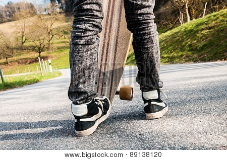 Legs and sneakers of a young boy and an edgewise longboard