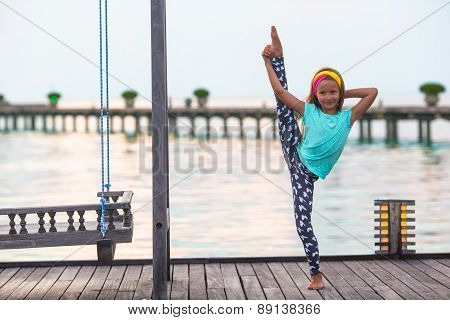 Silhouette of adorable little girl on wooden jetty at sunset