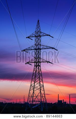 Electric High Voltage Power Post With Plant Factory In The Background At Sunset