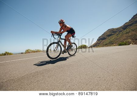 Young Woman Cycling On The Country Road