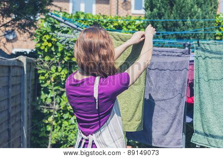 Woman Hanging Her Laundry In Garden