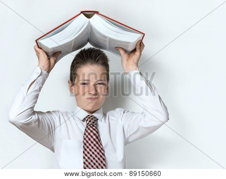 The displeased schoolboy teenager in a white shirt and a tie throws down a big red book on the gray background poster