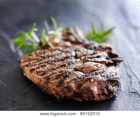 grilled prime rib beef steak with rosemary on slate
