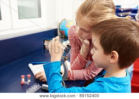 Girl And Boy Examines Drug For Microscope