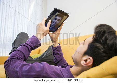 Young man sitting indoors  taking selfie or video chatting with