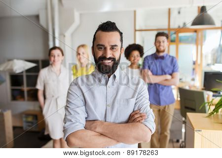 business, startup, people and teamwork concept - happy young man with beard over creative team in office