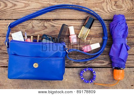 Blue women's purse. Items from open lady hand bag. Toned image.