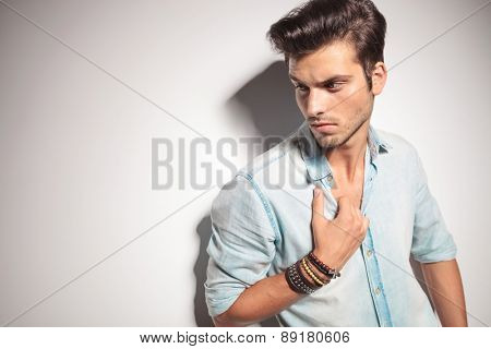 Close up picture of a handsome man pulling his shirt while looking down.