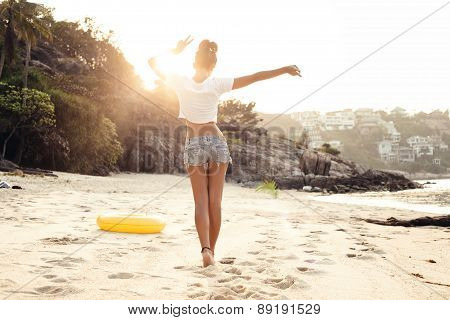 carefree woman dancing in the sunset on the beach. Outdoors lifestyle portrait of girl poster