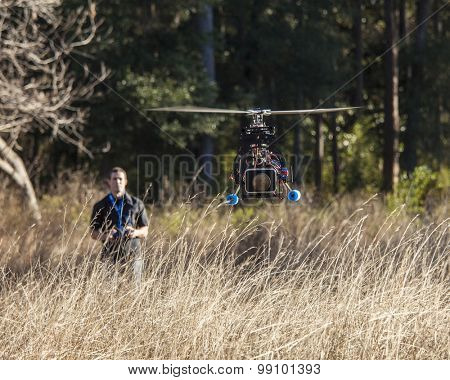 Man flying drone with camera on the front, man out of focus in background